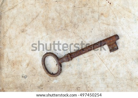 Rusty key on old parchment