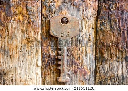 Rusty key on wooden background  - stock photo