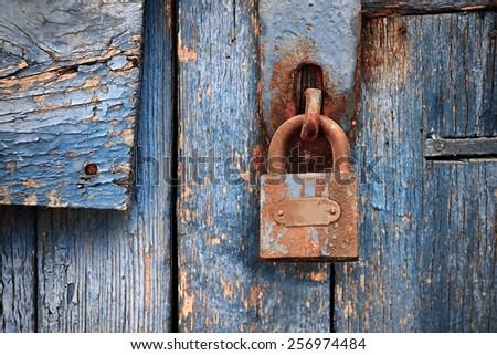 Rusty lock on old blue wooden door. - stock photo