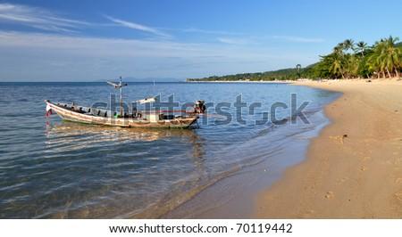 Rusty long tail boat on the sand seashore - stock photo