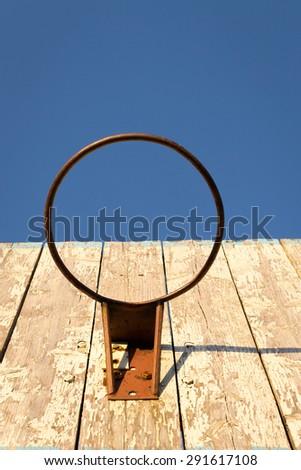 Rusty metal basketball hoop and backboard against a blue sky - stock photo