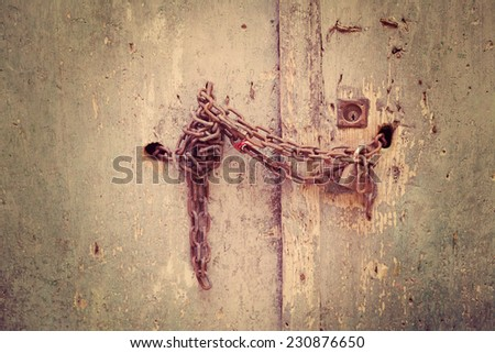 rusty metal chain on a wooden door. Processed for vintage tone effect - stock photo