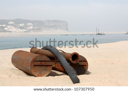 Rusty metal floats used for dredging sand on beach