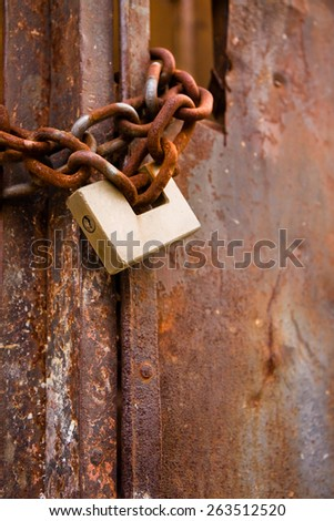 Rusty metal gate closed with padlock - concept image with copy space - stock photo