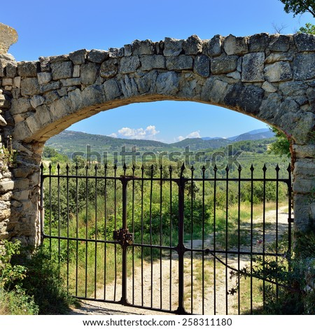 Rusty metal gate in the stone wall at the old medieval farmhouse in Provence, dirt road along countryside on background. France - stock photo