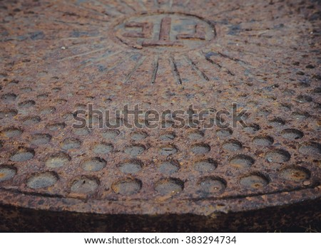 rusty metal sewer manhole casting with a relief surface - stock photo