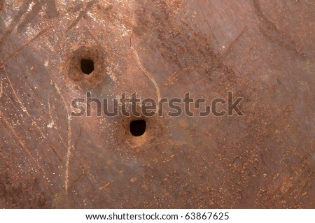 Rusty metal sheet with bullet holes - stock photo