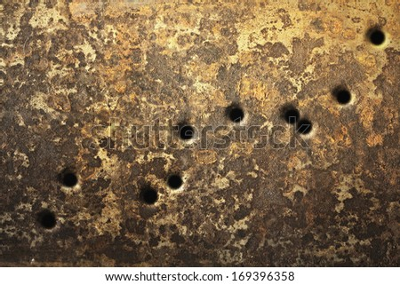 Rusty metallic surfaces perforated with bullet holes. - stock photo