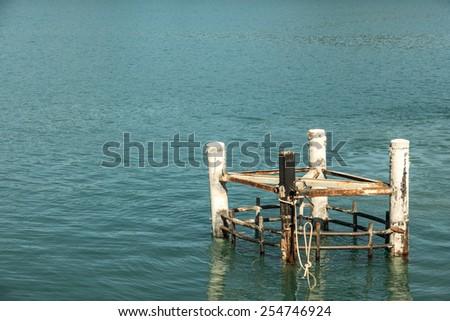 Rusty mooring bollard with ship ropes on docks - stock photo