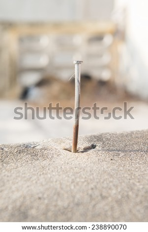 rusty nail in cement - stock photo
