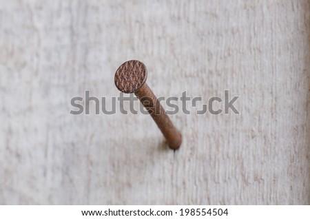 Rusty nail on wood background - stock photo
