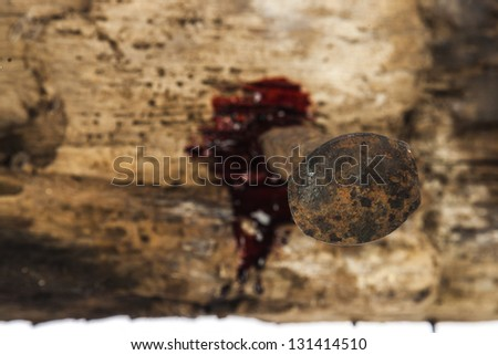 rusty nail on wood with blood drips focus on nail head - stock photo