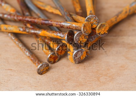 Rusty nail on wooden background - stock photo