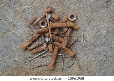 Rusty nuts bolts and nails on wooden background - stock photo