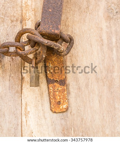 Rusty old iron chain with padlock attached to a wooden door - stock photo