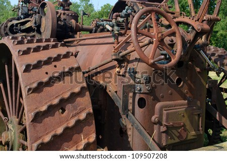 rusty old iron tractor decaying in a field - stock photo