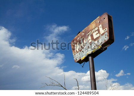 Rusty old motel sign with bullet holes and good grunge. - stock photo