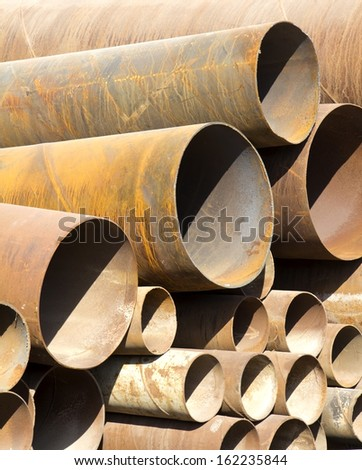 Rusty old pipes stacked up - stock photo