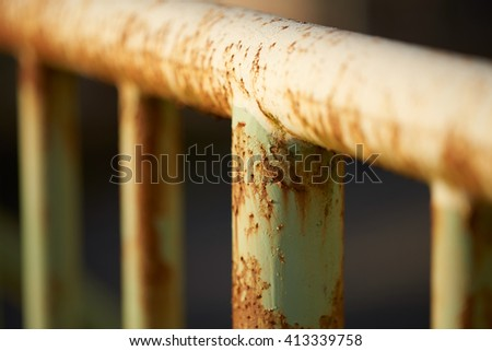 Rusty old poles on an iron fence with a very shallow depth of field. - stock photo