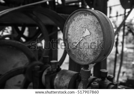 Rusty old pressure gauge in black and white.