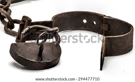 Rusty old shackles with padlock, key and open handcuff used for locking up prisoners or slaves between 1600 and 1800.  - stock photo