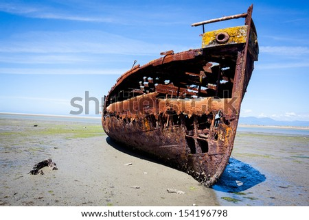 Rusty old shipwreck trapped on a beach. - stock photo