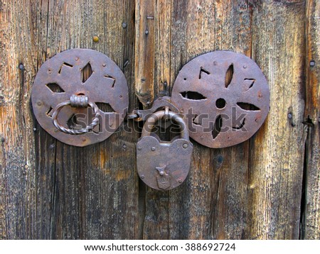 rusty padlock on an old wooden door - stock photo