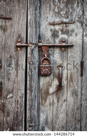 Rusty padlock on an old wooden door of the indian house - stock photo