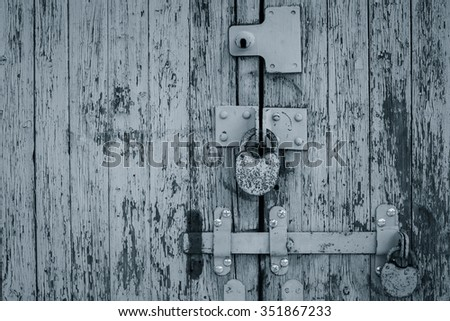 Rusty padlocks on an old painted wooden gate. Black and white