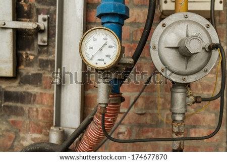 Rusty Pressure Gauge connected to pipes with brick wall behind - stock photo