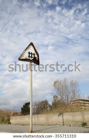 Rusty Rail Crossing Signboard with a Blue Sky as Background