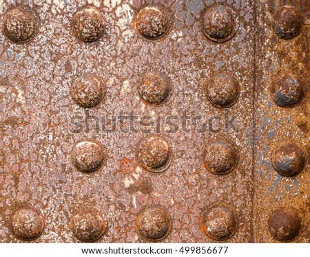 Rusty rivets of iron riveted steel construction background texture pattern