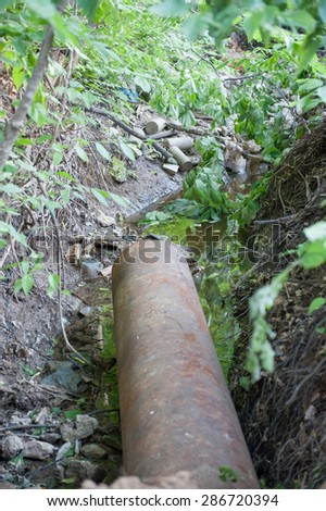 Rusty sewer pipe feeds into a creek - stock photo