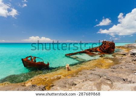 Rusty ship wreckage on a peaceful beach in the Bahamas