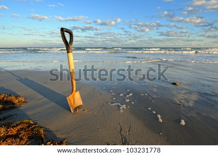 Rusty Shovel in Wet Sand at the Beach. A rusty shovel digging in wet sand along a shoreline under a partly cloudy blue sky. - stock photo