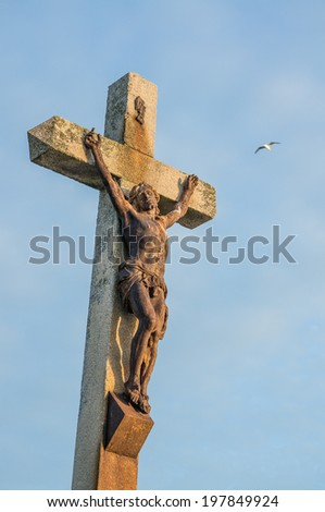 Rusty statue of Jesus on cross, Barfleur, Normandy, France - stock photo
