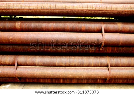 Rusty steel pipes bunch on the rack in warehouse