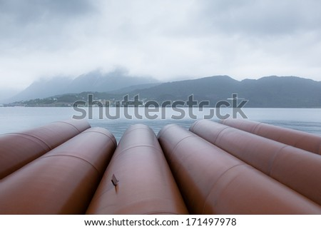 Rusty steel pipes stored near water in rainy weather - stock photo