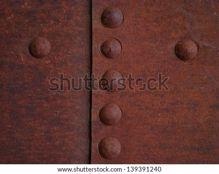 Rusty steel plates with seven rivets - stock photo
