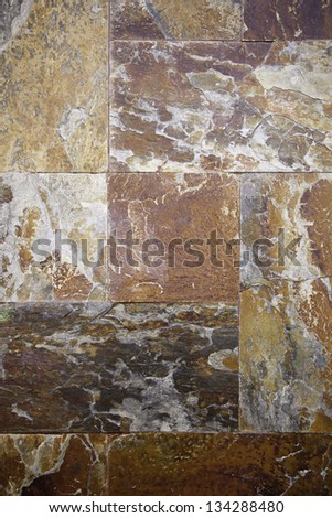 Rusty stone wall, detail of a wall of stone tiles, textured background in the city - stock photo