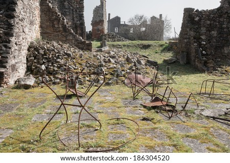 Rusty table and chair framework in the ruin, Oradour-sur-Glane, France. In this village, 642 of its inhabitants were massacred by a German Waffen-SS company in the second world war. - stock photo