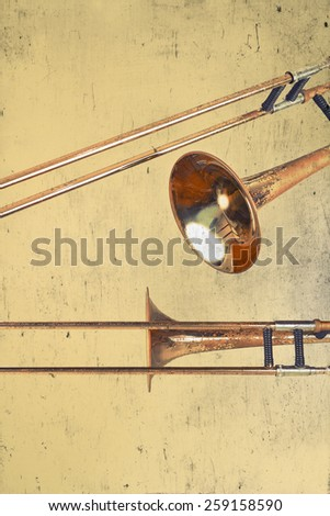 Rusty Trombones in grunge style textured musical background - stock photo