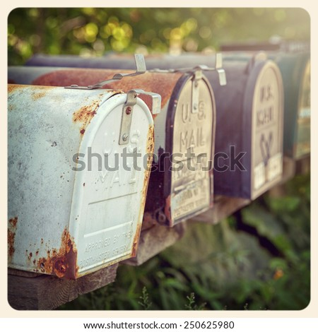 Rusty US mailboxes in the afternoon sun. . Filtered to look like an aged instant photo. - stock photo