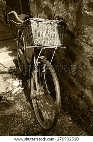 Rusty vintage bicycle with wicker basket leaning on a stone wall. Brittany, France. A game of light and shadow. Aged photo. Sepia. - stock photo