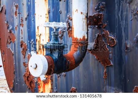 rusty water valve and tank - stock photo