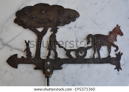 Rusty weather vane with pastoral scene farmer ploughing with horse. Vintage metal architectural ornament for showing wind direction. - stock photo