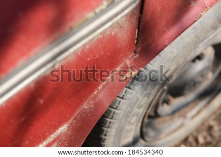 Rusty wheel and cracked paint of a very old car - stock photo
