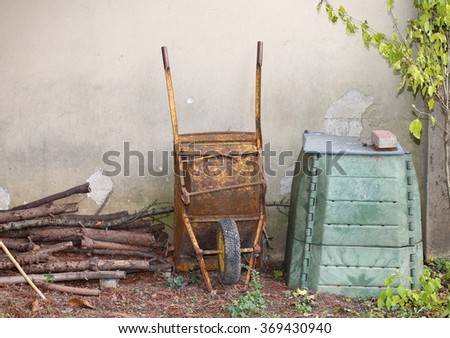 rusty wheelbarrow in the garden and the big green container for compost to be used as natural fertilizer for the garden ecology - stock photo
