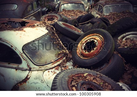 Rusty wheels and autumn leaves lying on vintage cars in an old auto graveyard. - stock photo