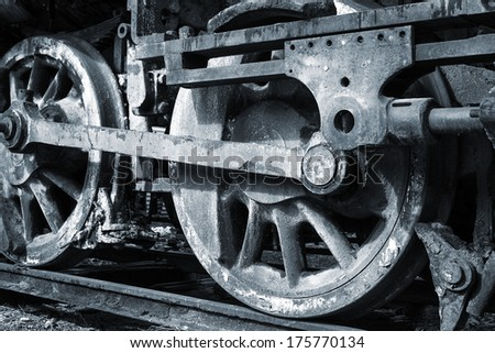 rusty wheels of old steam locomotive close up - stock photo